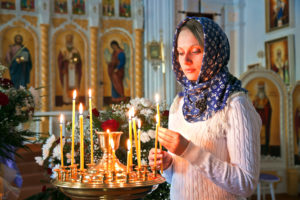 Girl with a candle in the Orthodox Church.